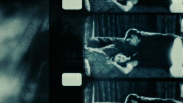 Black and white scene from Twilight with Edward lying on top of Bella on a couch with her face turned towards the viewer.