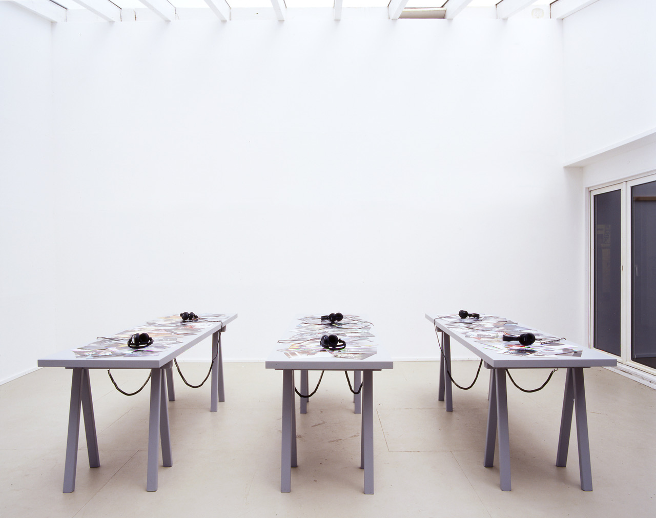 Photograph of the three tables with sets of headphones on them at the PLOTS installation.