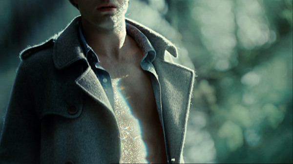A close-up shot showing Edward's torso from above the waist to just above his mouth. His shirt and jacket are open and the light is reflecting off of his skin.