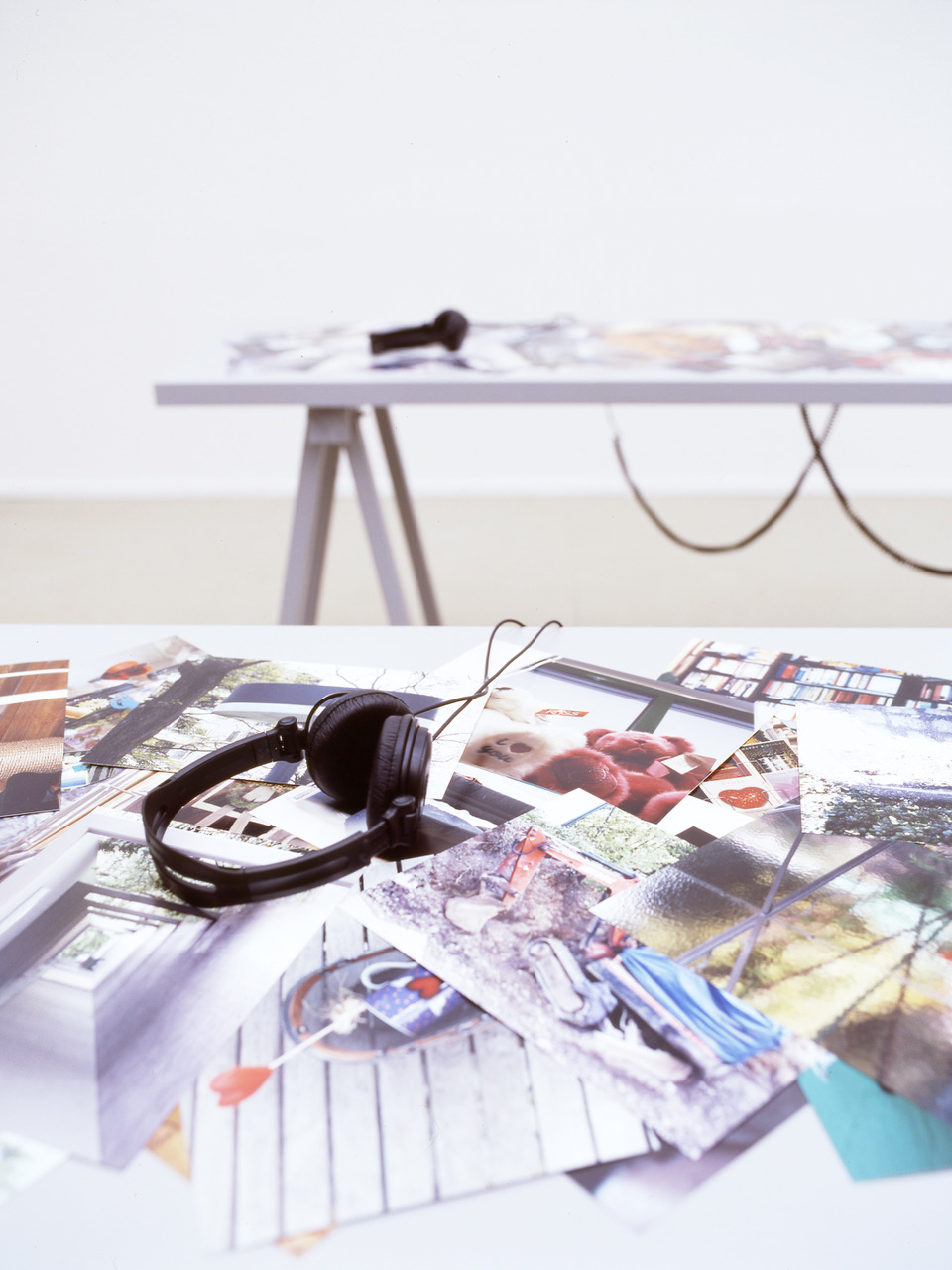 A close-up picture showing the top of one table in the PLOTS installation, which looks like it is printed with color photographs of a variety of everyday things. There are headphones on the table.
