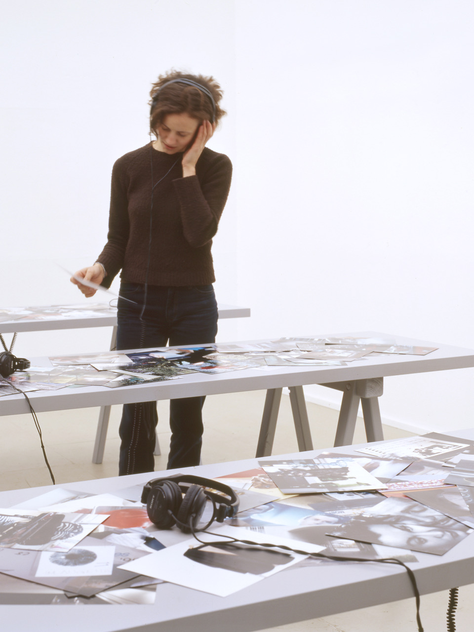 Photograph of the PLOTS installation showing one person standing at a table using the headphones to listen to the installation audio.