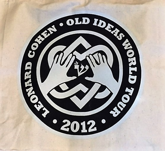 """A circular logo on a white background. The circle is black with white text around the rim reading """"Leonard Cohen Old Ideas world Tour 2012"""". The interior of the cirlce contains a white design of two interlocking hearts and two hands."""